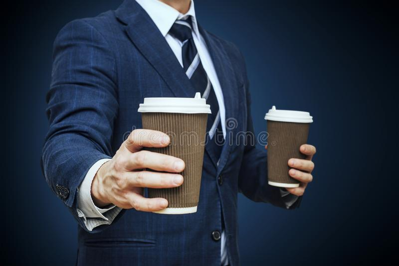 Businessman offering coffee in paper cup. Businessman offers a cup of coffee. Businessman holding two disposable coffee cup stock photos