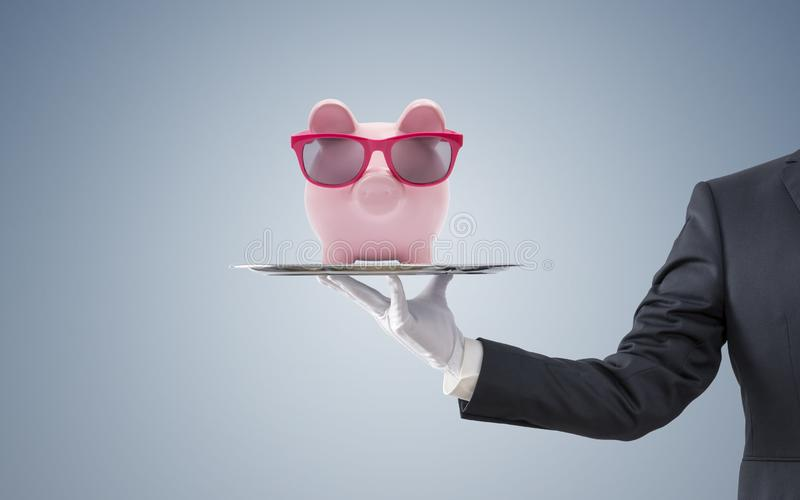 Businessman offering piggy bank with pink glasses royalty free stock photo