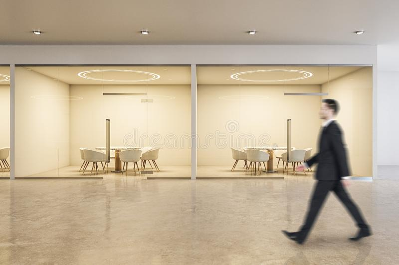 Businessman in office. Blurry businessman walking in modern spacious office interior with copy space and daylight. Workplace and corporation concept stock photos