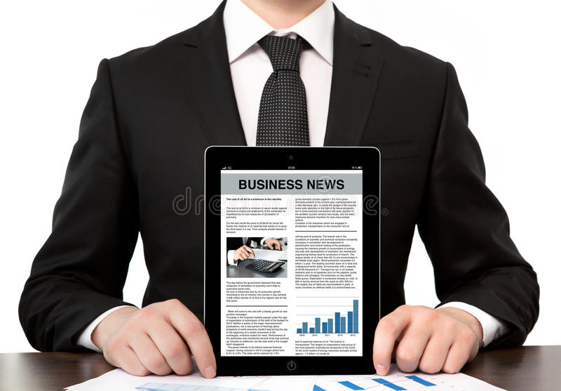 businessman at the office holding a computer tablet with business news on screen royalty free stock photography