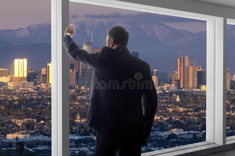 Businessman in an office looking at the view of downtown Los Angeles stock image