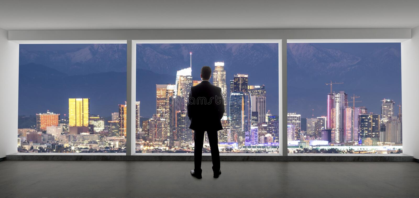 Businessman in an office looking at the view of downtown Los Angeles stock photos