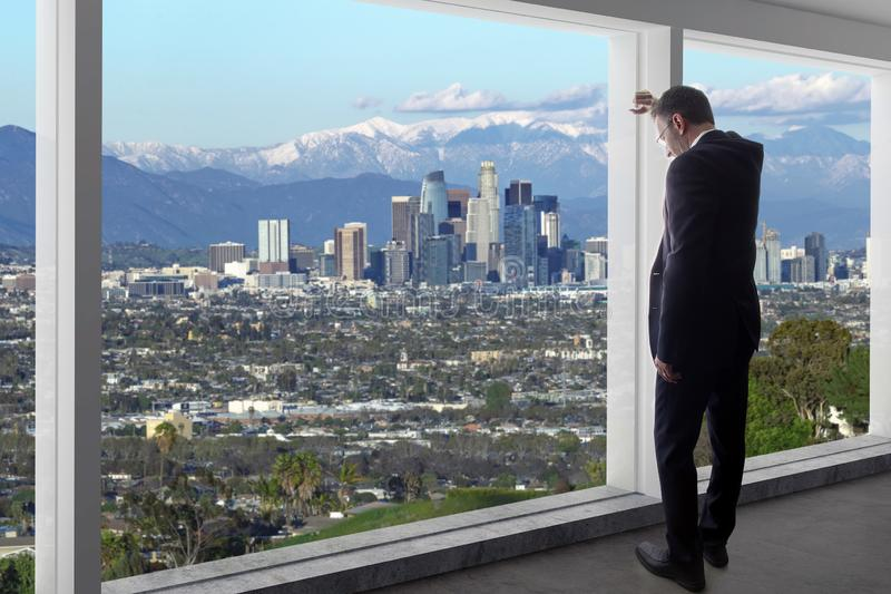 Businessman in an office looking at the view of downtown Los Angeles in Winter royalty free stock photos