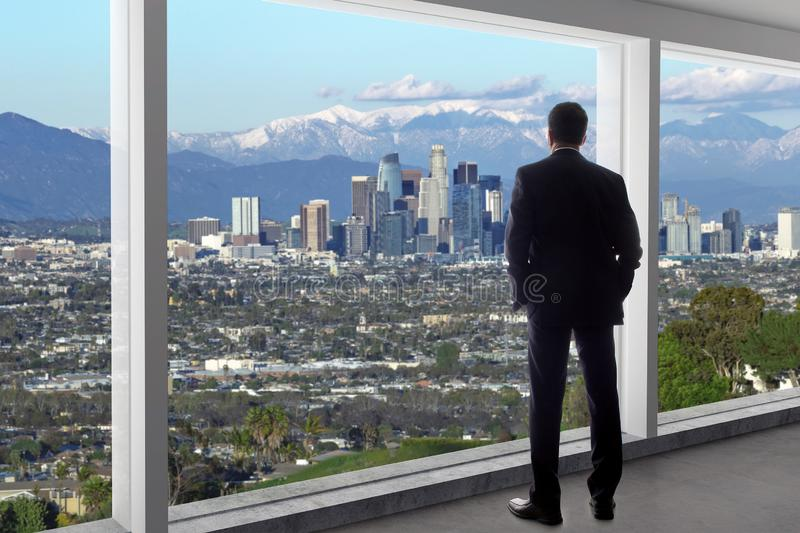 Businessman in an office looking at the view of downtown Los Angeles in Winter royalty free stock images