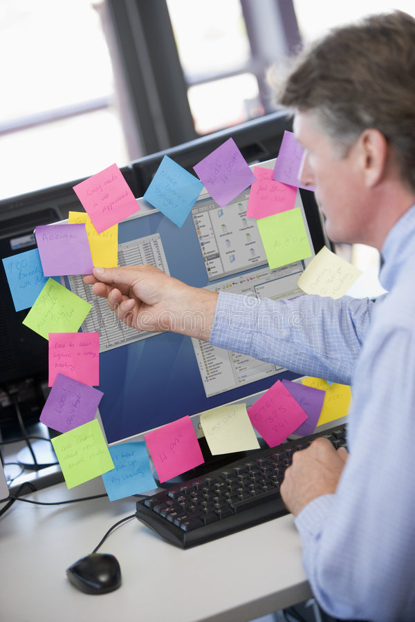 Businessman in office at monitor with notes on it. Taking one off royalty free stock photos