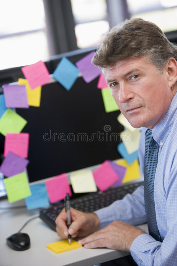 Businessman in office at monitor with notes. On it writing looking towards camera royalty free stock photo