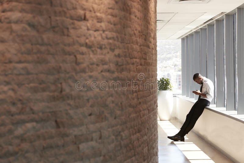 Businessman In Office Sending Text Message On Mobile Phone stock image