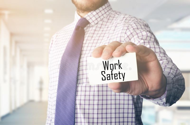 Businessman in office showing card with text: Work Safety. Businessman in office showing card with text royalty free stock photo
