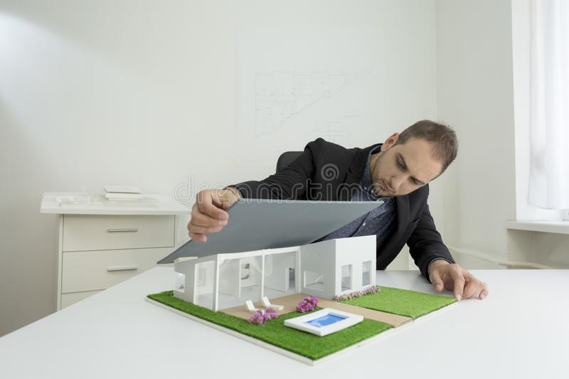 Businessman fixes the architecture of a house model with roof. Businessman in office sitting at desk looking over a house model. Thoughtful Architect thinking stock photography