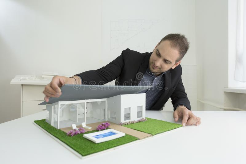 Businessman fixes the architecture of a house model with roof. Businessman in office sitting at desk looking over a house model. Thoughtful Architect thinking royalty free stock photo