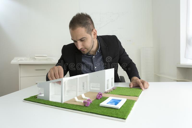 Businessman fixes the architecture of a house model with roof. Businessman in office sitting at desk looking over a house model. Thoughtful Architect thinking royalty free stock image