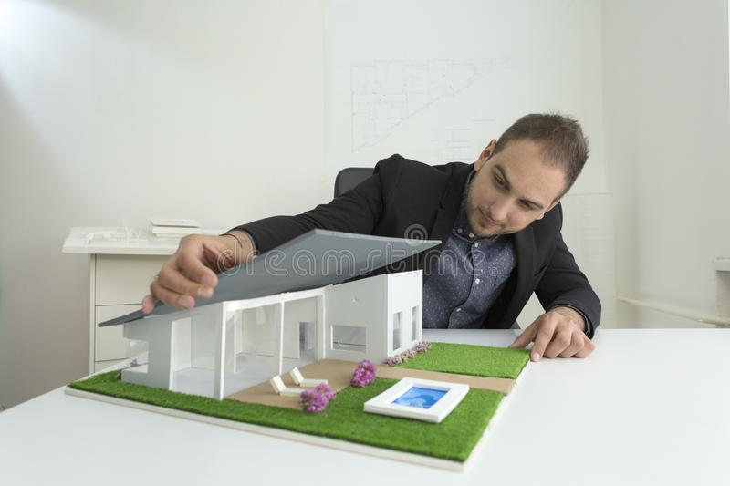 Businessman fixes the architecture of a house model with roof. Businessman in office sitting at desk looking over a house model. Thoughtful Architect thinking stock image