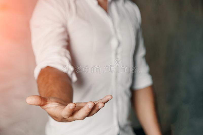 Businessman with open palm offering something. Close-up of young businessman`s hand in concept of holding or giving stock images