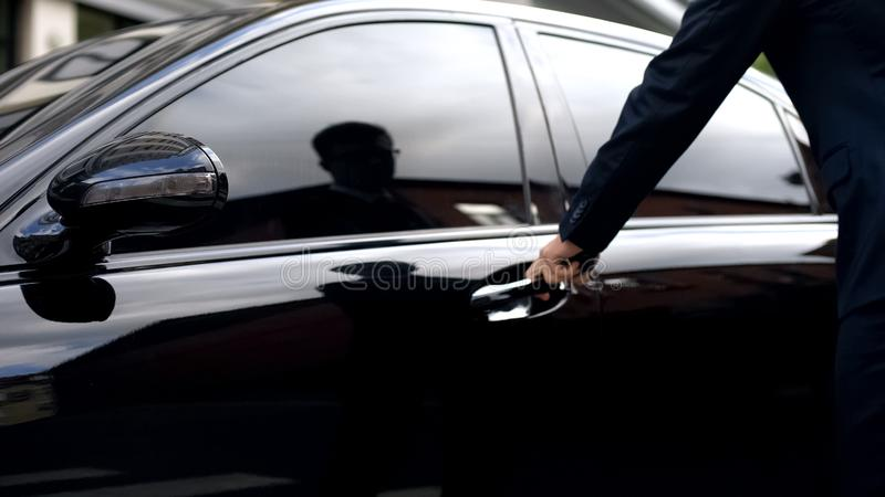 Businessman opening car, renting luxurious premium class auto for business trip stock photos