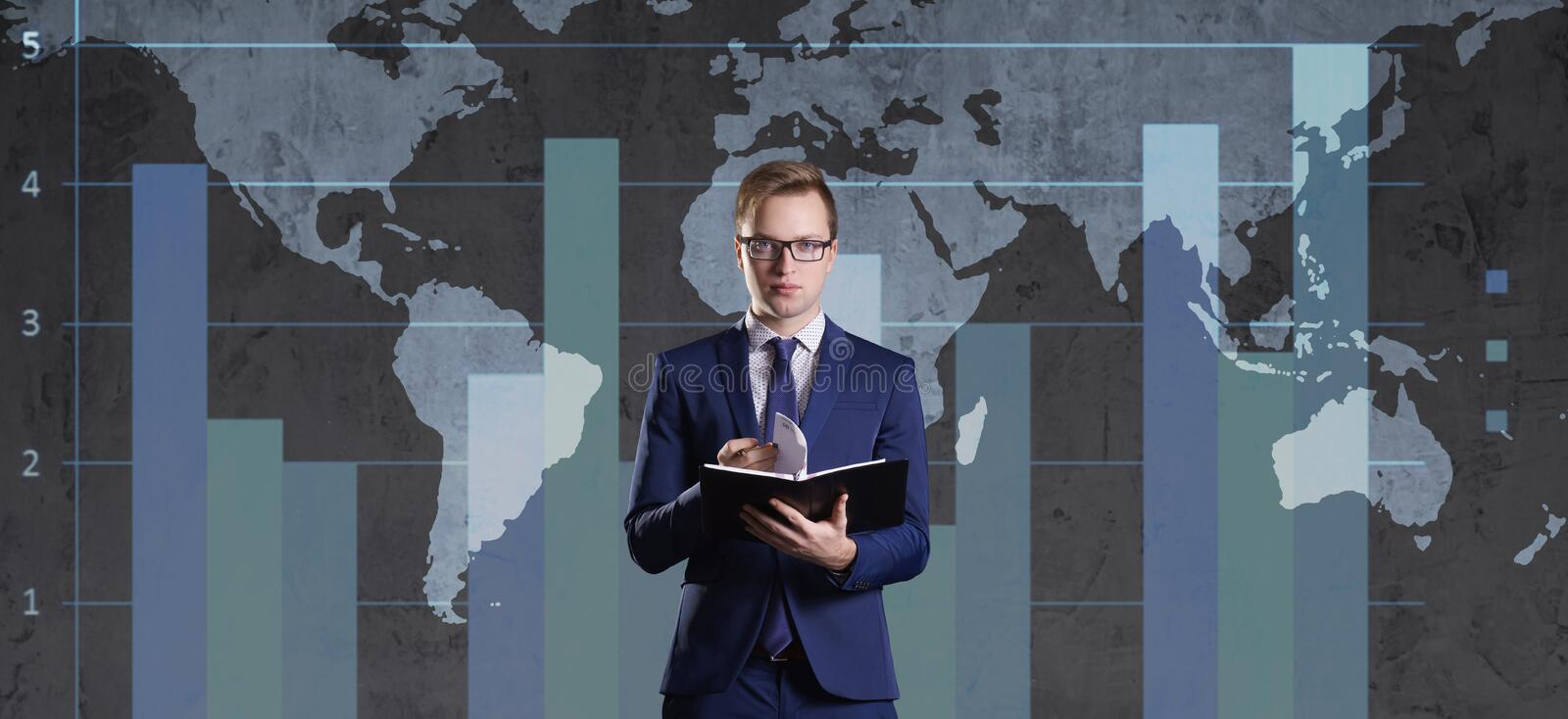 Businessman with organizer standing over diagram. World map background. Business, globalization, capitalism concept. stock photography
