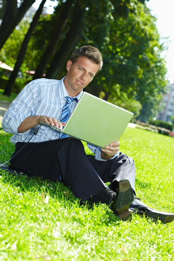Businessman outdoor. Relaxed businessman sitting in grass beside laptop computer, reading newspaper royalty free stock images