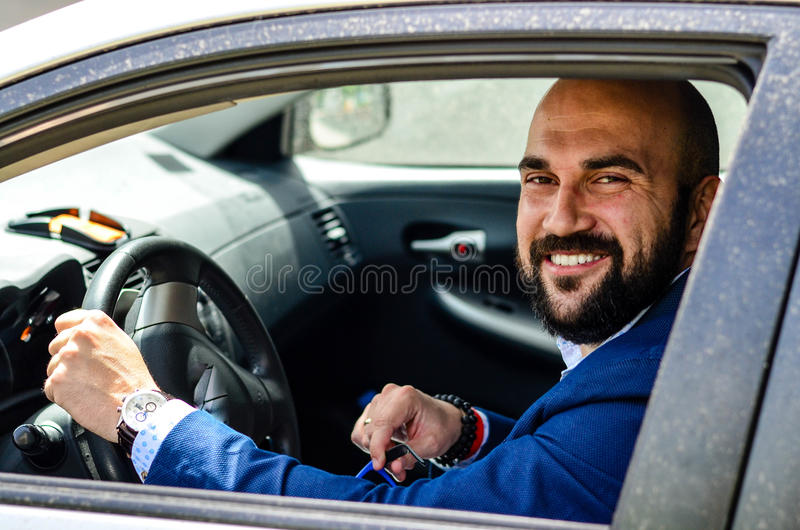 Businessman outdoor. Handsome bearded smiling businessman at the car royalty free stock image