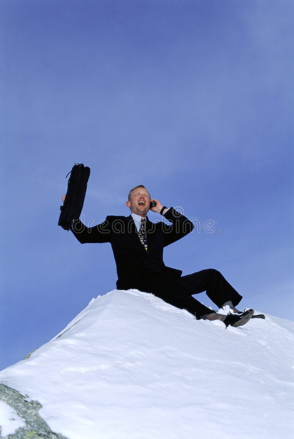 Businessman outdoors on snowy mountain using phone. Businessman outdoors on snowy mountain using cellular phone royalty free stock images