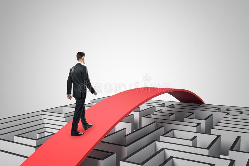 Businessman overcoming maze. Businessman going over maze on red path. Challenge and overcome concept stock images