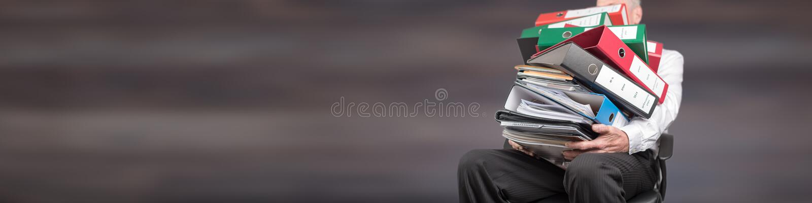 Businessman overworked carrying a pile of binders and folders. On grey background royalty free stock photography