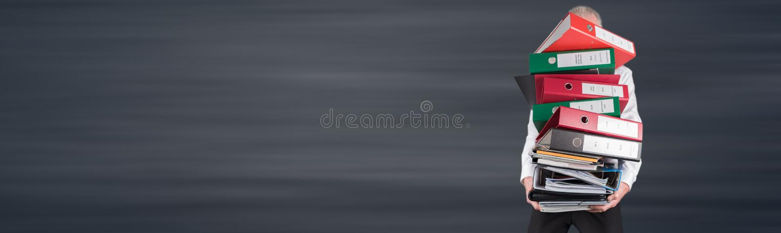 Businessman overworked carrying a pile of binders and folders. On grey background stock photo