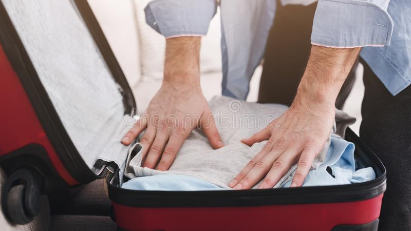 Businessman packing clothes into travel bag, closeup royalty free stock photo