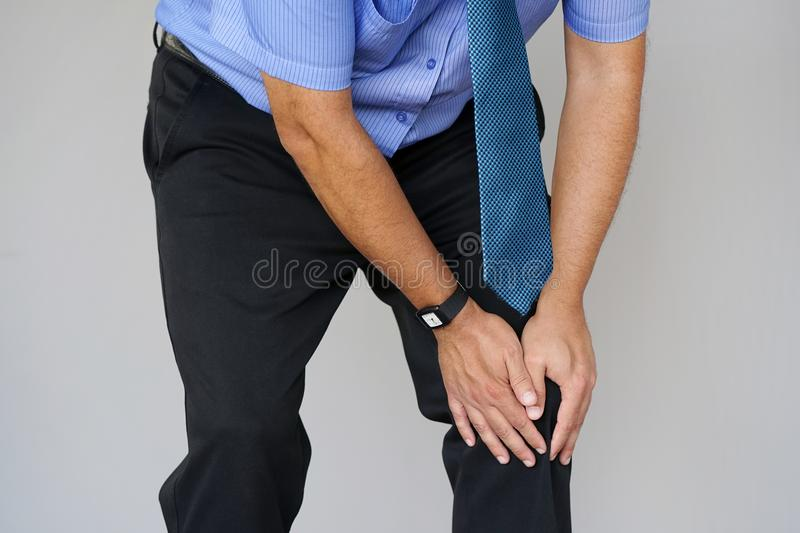 Businessman Pain in the knees of a man. Pain In Knee. Close-up Businessman Leg With Painful Kneeson on gray background. Man Feeling Joint Pain, Having Health stock photos