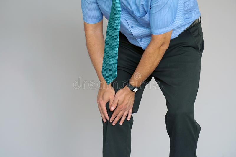 Businessman Pain in the knees of a man. Pain In Knee. Close-up Businessman Leg With Painful Kneeson on gray background. Man Feeling Joint Pain, Having Health royalty free stock image