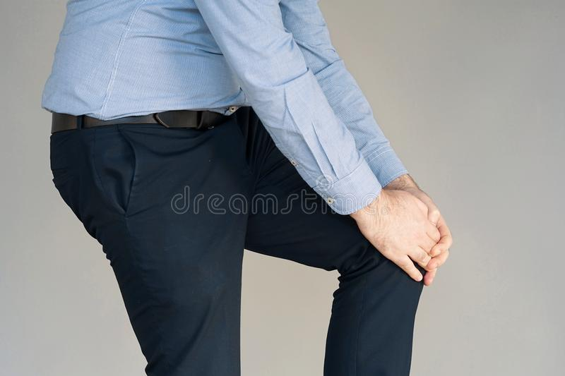 Businessman Pain in the knees of a man. Pain In Knee. Close-up Businessman Leg With Painful Kneeson on gray background. Man Feeling Joint Pain, Having Health stock photo