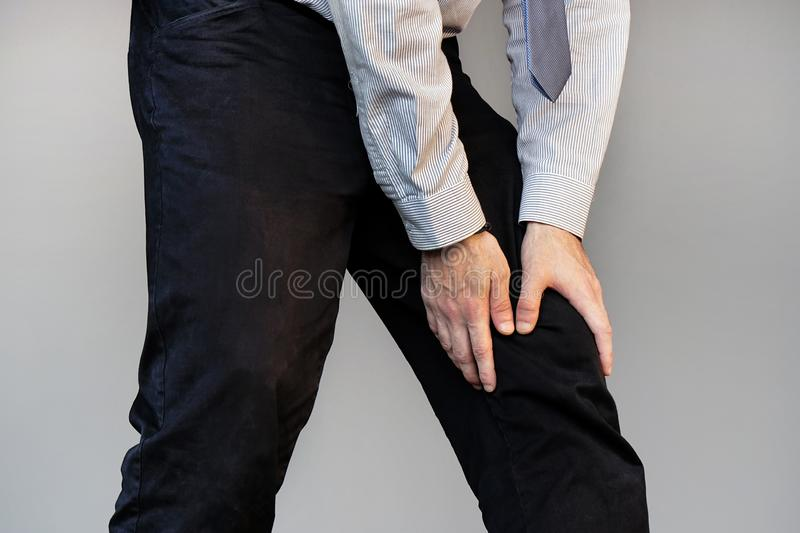 Businessman Pain in the knees of a man. Pain In Knee. Close-up Businessman Leg With Painful Kneeson isolated on gray background. Man Feeling Joint Pain, Having stock photos