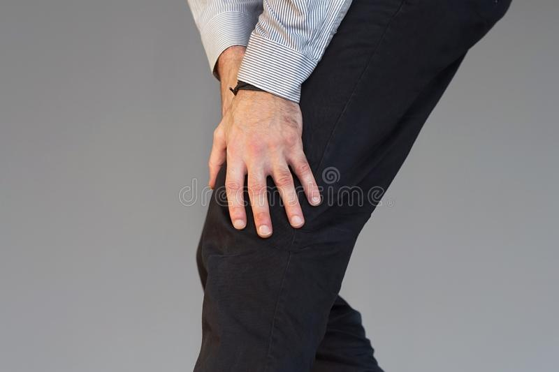 Businessman Pain in the knees of a man. Pain In Knee. Close-up Businessman Leg With Painful Kneeson isolated on gray background. Man Feeling Joint Pain, Having stock photo
