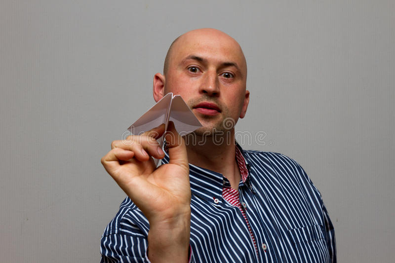 Businessman with paper airplane. Playful young man in formalwear holding paper airplane and smiling while standing royalty free stock photos