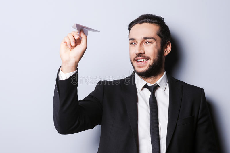 Businessman with paper airplane. Playful young man in formalwear holding paper airplane and smiling while standing against grey background stock photo