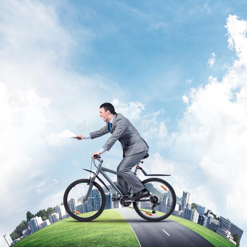 Businessman with paper documents in hand. On bike. Deadline for paperwork. Corporate employee in business suit riding bicycle on highway. Cyclist on world round royalty free stock images