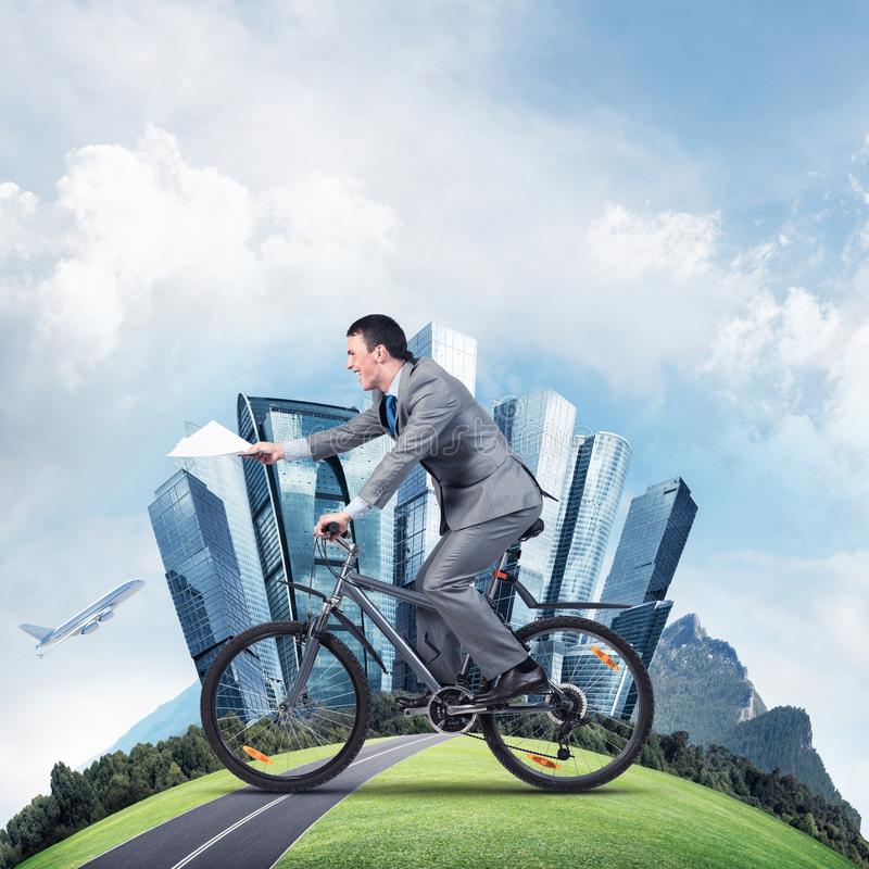 Businessman with paper documents in hand. On bike. Deadline for paperwork. Corporate employee in business suit riding bicycle on highway. Cyclist on world round royalty free stock photos