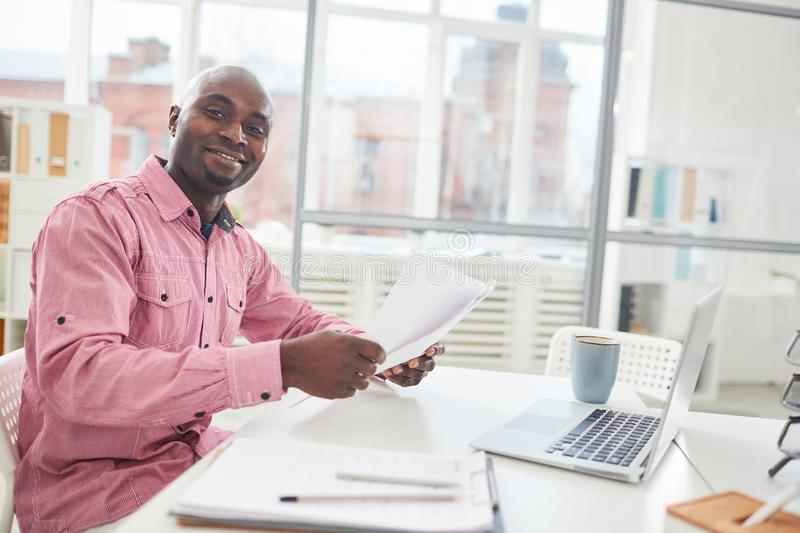 Businessman with papers. Happy young African-american businessman with papers sitting by desk and analyzing information during working day royalty free stock photography
