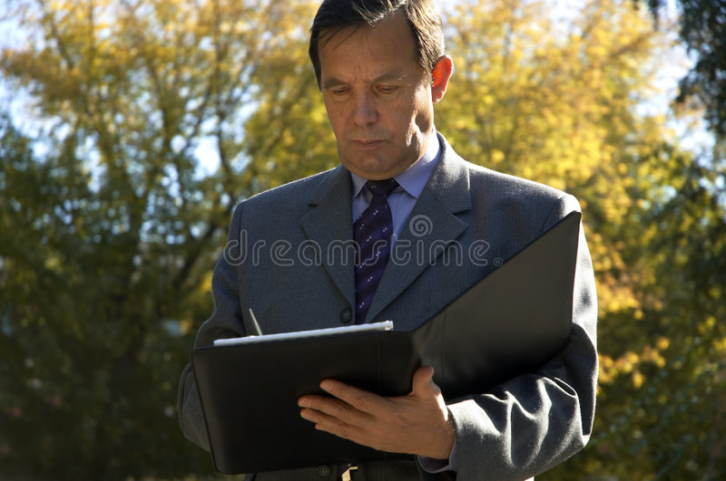 Businessman with papers outside stock image