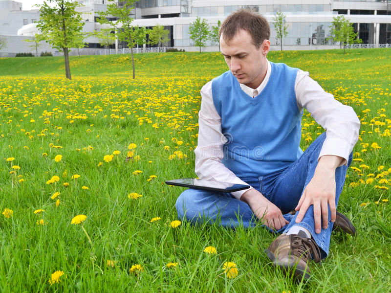 Businessman at the park with tablet stock image