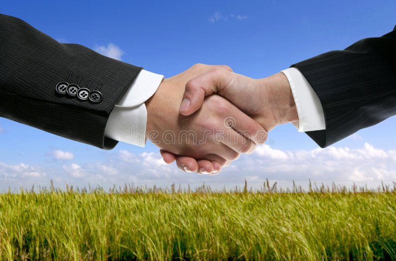 Businessman partners shaking hands in nature. Businessman teamwork partners shaking hands in green nature royalty free stock photo