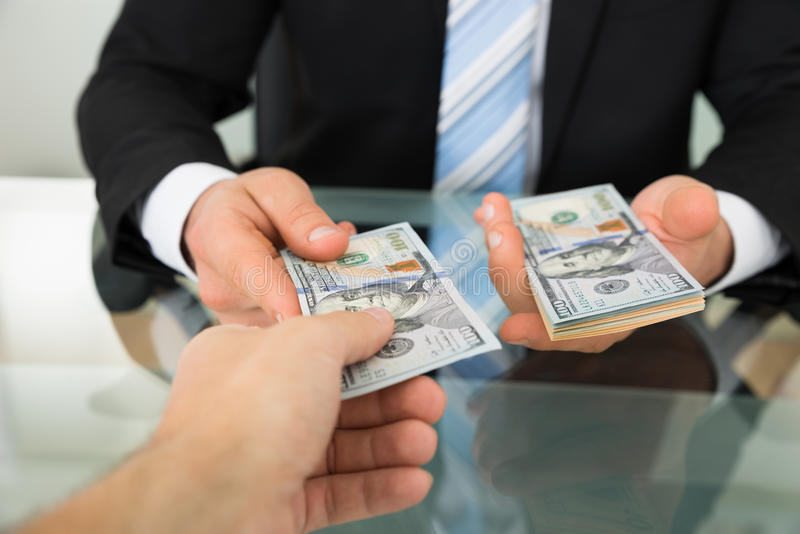 Businessman passing money to colleague at table royalty free stock images