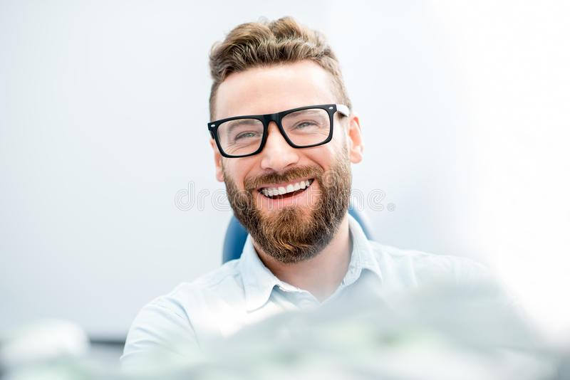 Businessman patient at the dental office. Handsome businessman with great smile sitting on the dental chair stock photos