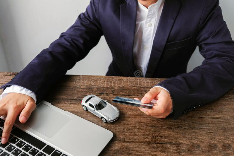 Businessman paying a credit card by laptop with car model on the. Wooden table , The concept of trading and buying cars on the Internet royalty free stock photos
