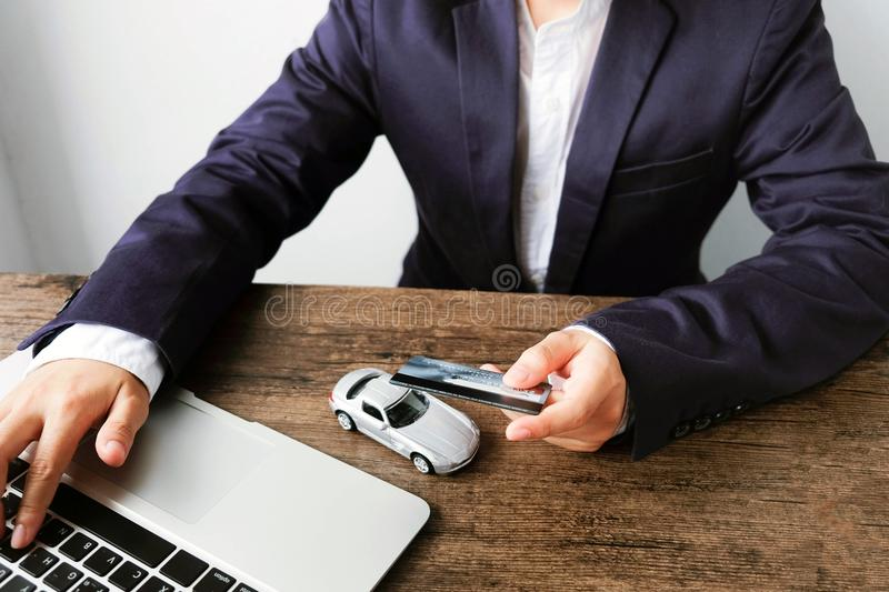 Businessman paying a credit card by laptop with car model on the. Wooden table , The concept of trading and buying cars on the Internet stock photo