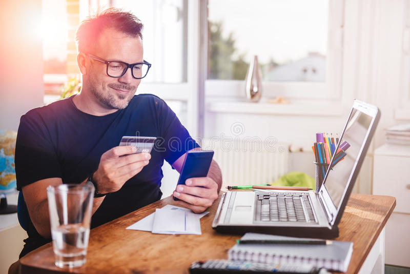 Businessman paying with credit card on smart phone stock photos