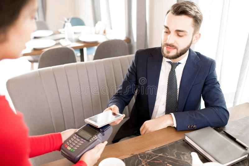 Businessman paying for lunch with smartphone. Content handsome bearded businessman with mustache using smartphone for NFC payment while waitress holding credit stock image