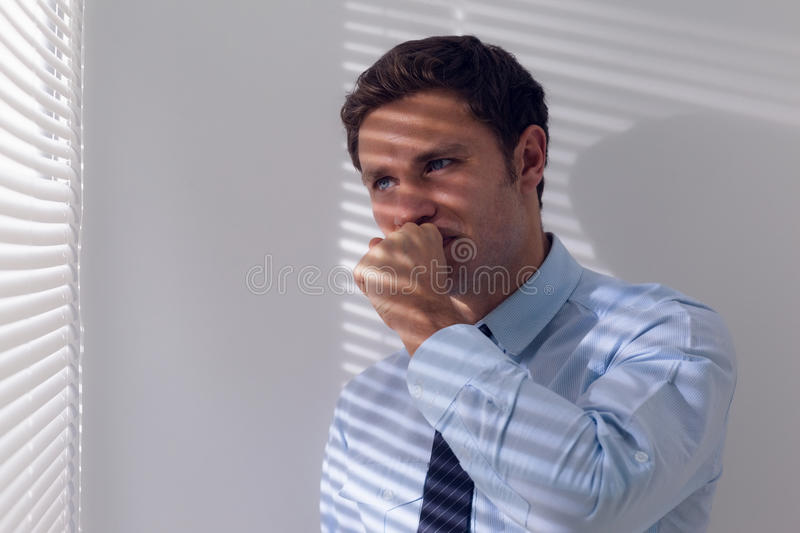 Businessman peeking through blinds while coughing. Young businessman peeking through blinds while coughing in office stock photo