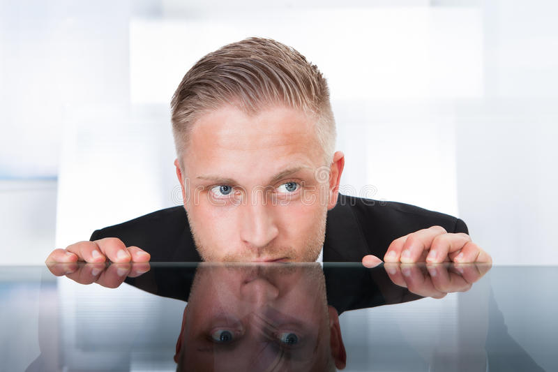 Businessman peering furtively over the top of his desk. As he spies on a colleague or tries to remain out of the firing line to avoid any blame for a problem stock photos