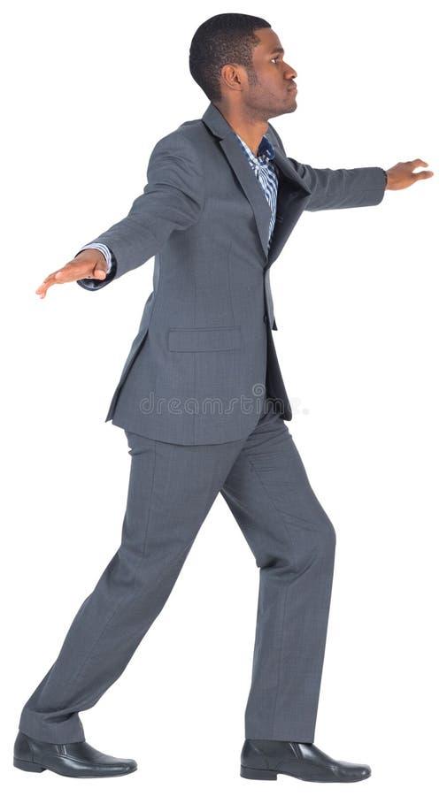 Businessman performing a balancing act stock photo