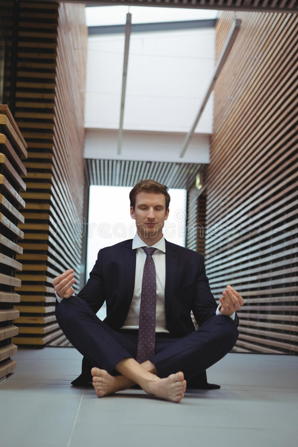 Businessman performing yoga in the corridor stock photos