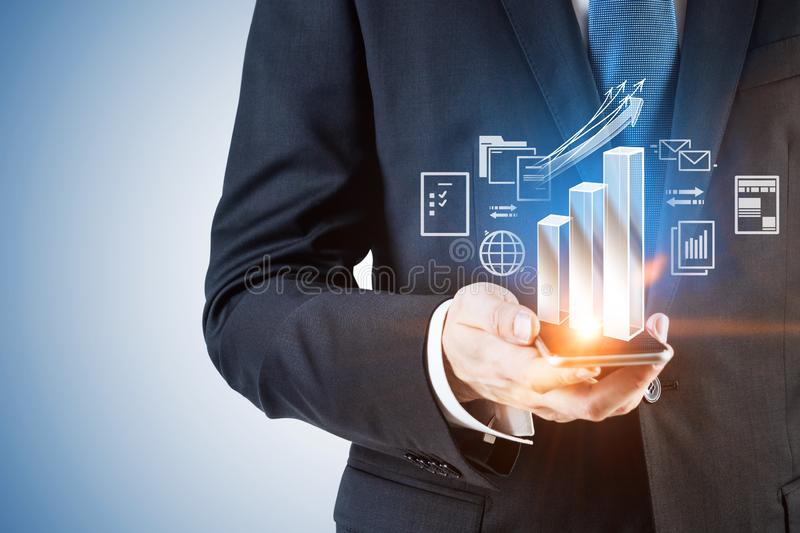 Businessman with phone, bar chart net interface. Hand of unrecognizable businessman holding smartphone with growing bar chart and internet icons interface and royalty free stock photo